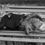 Homeless elderly woman sleeps on bench in Park