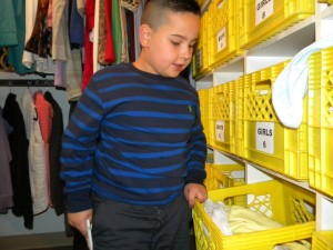 Nicolas inspects bins of donated clothes and shoes.